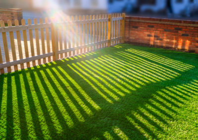 sun shining through a wooden picket fence onto an artifical grass lawn